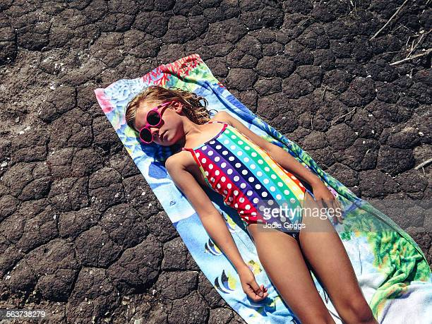 Child sun baking on towel on dry parched ground