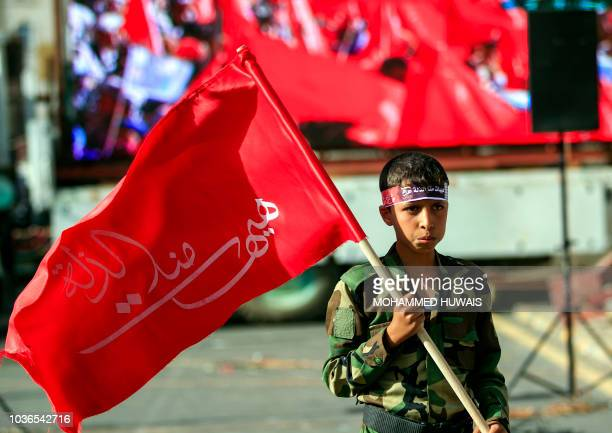 A child supporter of Yemen's Shiite Huthi rebels waves a flag as others march in Sanaa during a rally commemorating the fourth anniversary of their...