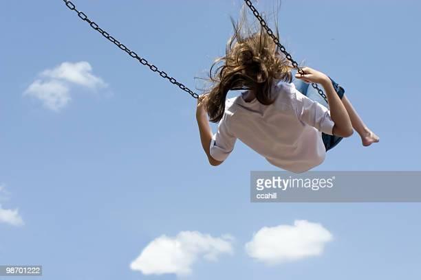 Child swinging high against blue sky