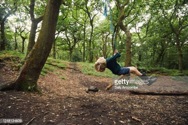 child swinging on a rope swing - positive emotion stock pictures, royalty-free photos & images