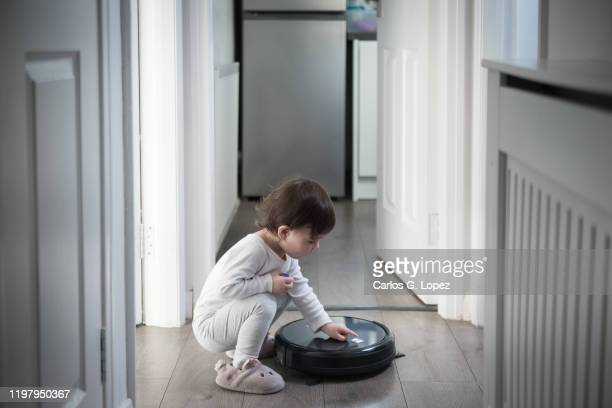 child switches on a robot vacuum in the corridor - play off stock pictures, royalty-free photos & images