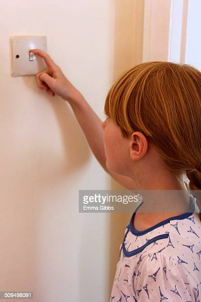 Child switching off light switch