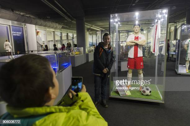 A child takes a photo of another child posing next to Robert Lewandowski made of Lego bricks during a lego exhibition at Wroclaw Stadium in Wroclaw...