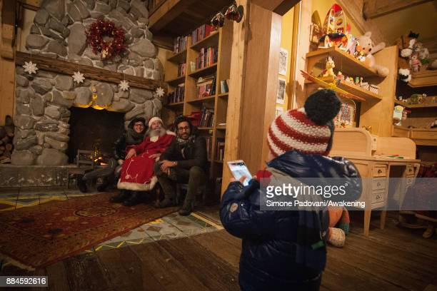 A child takes a picture of his parents with Santa Claus in his house in the Reggia of Venaria on December 2 2017 in Turin Italy