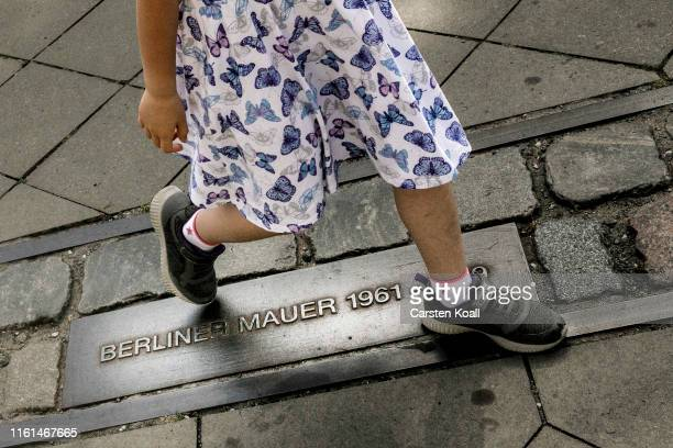 A child takes a step over a metal plate labeled Berlin Wallat a memorial to the Berlin Wall in Bernauer Strasse on August 13 2019 in Berlin Germany...
