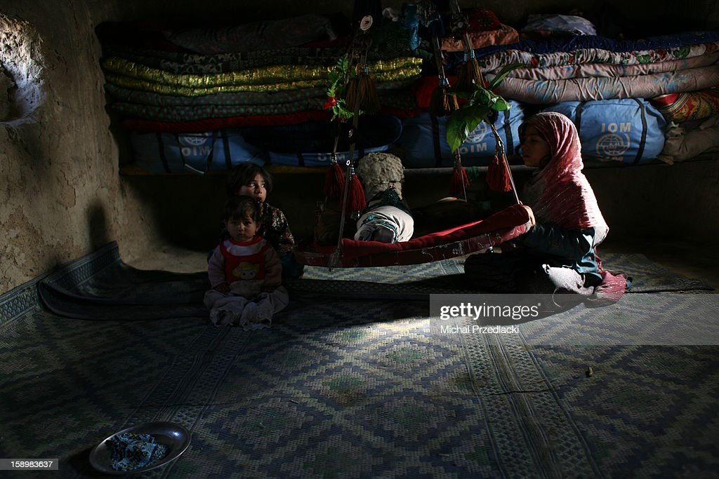 CONTENT] A child takes care of an infant inside her one-room mud hut. December 2011, Kabul, Afghanistan. In Bagrami, a suburbs of Kabul maybe 30 minutes away from the city center, there is a shanty town of mud-built huts of refugees that escaped horrors of war in the southern provinces of Afghanistan. This camp has steadily grown as bombardments continue and families from different districts of Helmand arrive in batches to join those that fled earlier. Although families fled the fighting temporarily, to many it is the third or fourth year since they arrived to Kabul, and live on a verge of existence.