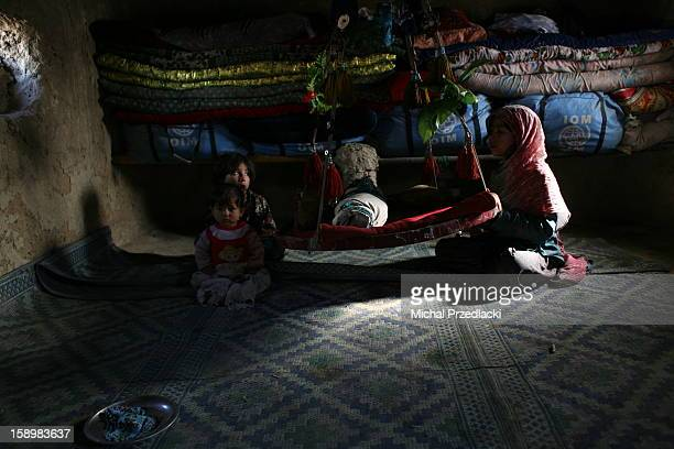 CONTENT] A child takes care of an infant inside her oneroom mud hut December 2011 Kabul Afghanistan In Bagrami a suburbs of Kabul maybe 30 minutes...
