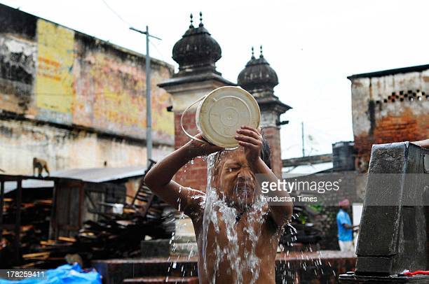 Child takes his morning bath on August 27, 2013 in Ayodhya, India. Two days after the failed Parikarma attempt by Vishwa Hindu Parishad , streets in...