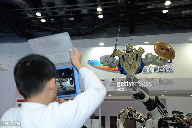 A child takes photos of a Gundam robot at the World Robot Exhibition 2015 at China National Convention Center on November 23 2015 in Beijing China...