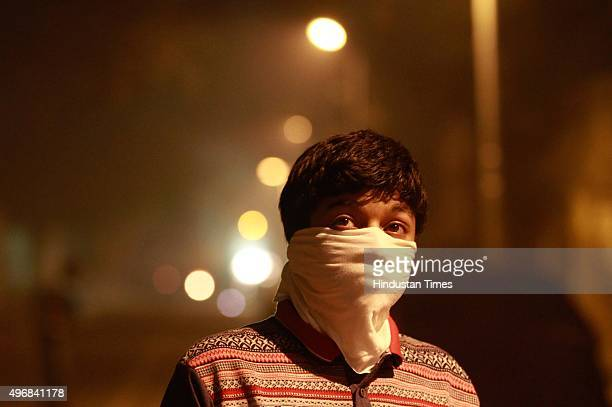 A child takes precautions against air pollution as fire crackers add to the smog and air pollution on Diwali on November 11 2015 in New Delhi India...