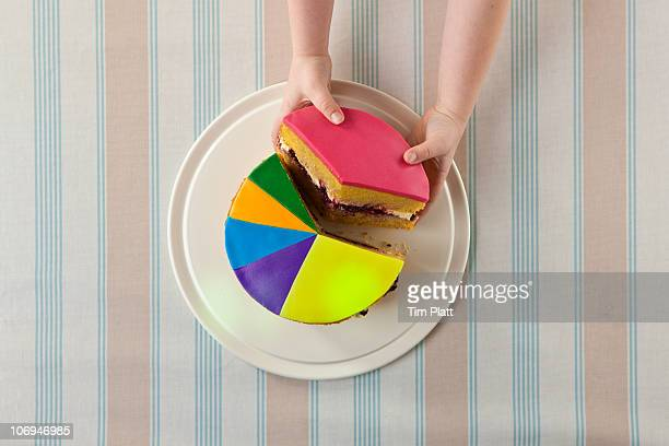 a child takes slice of a 'pie chart' cake. - kuchen stock-fotos und bilder