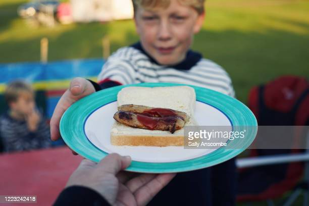 child taking a plate of food - sausage stock pictures, royalty-free photos & images