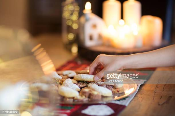 Child taking a traditional German Christmas cookie off a plate on a table