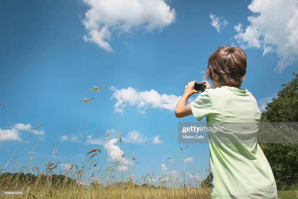 child taking photos of airplanes : Stock Photo