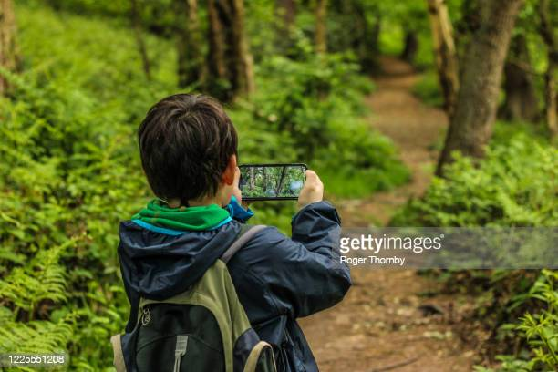 a child taking photos on a country footpath - nature reserve stock pictures, royalty-free photos & images