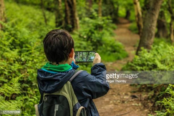 un bambino che scatta foto su un sentiero di campagna - nature reserve foto e immagini stock