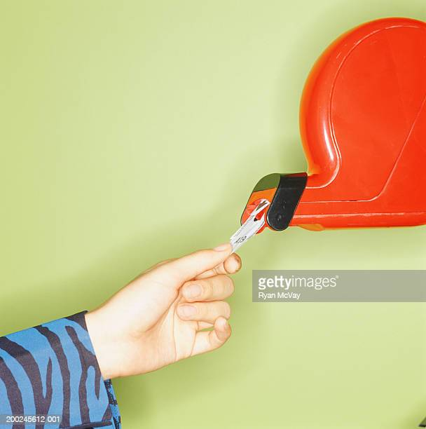 Child (12-13) taking ticket from dispenser, Close-up of hand