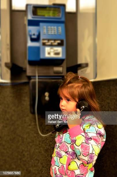 child talking on public telephone - rafael ben ari 個照片及圖片檔