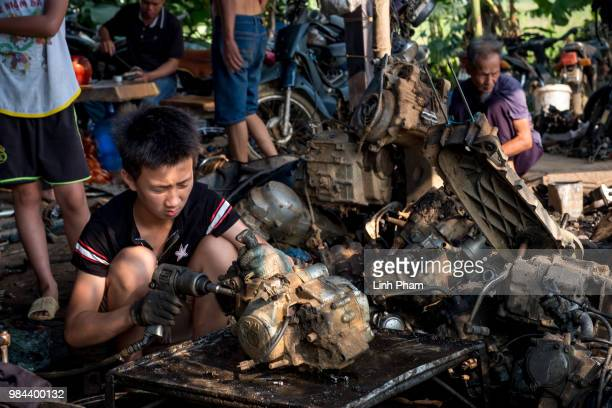 A child tears apart a motorcycle engine at his family motorcycle scrapyard on June 7 2018 in Te Lo Village Yen Lac District Vinh Phuc Province...