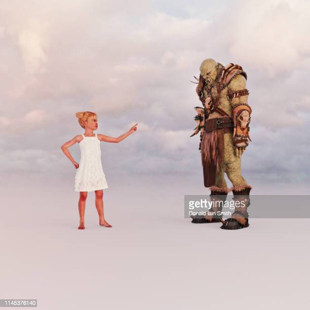 child telling off ogre in warrior clothes - モンスター ストックフォトと画像