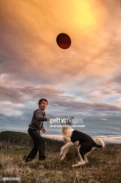 Child throwing a disc to his dog