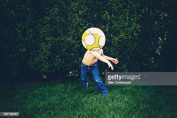 child throwing soccer ball in grass