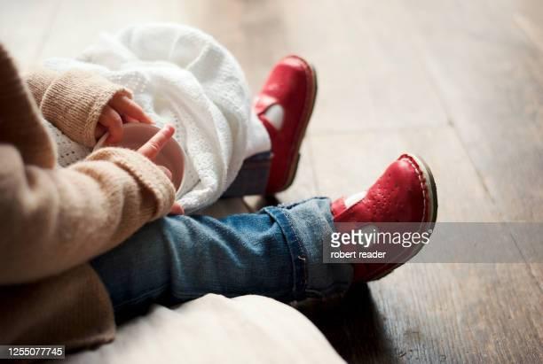 child toddler wearing red shoes sitting on floor - sapato vermelho imagens e fotografias de stock