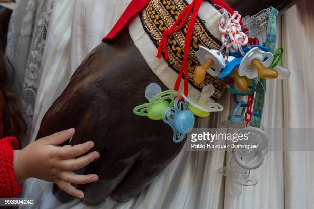 A child touches the hand of a giant carrying babies dummies during the Comparsa de Gigantes y Cabezudos or Giants and Big Heads parade on the second...