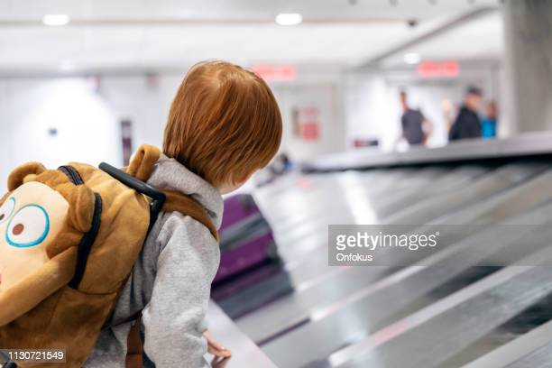 child traveler waiting for suitcase on conveyor belt in airport - baggage claim stock pictures, royalty-free photos & images