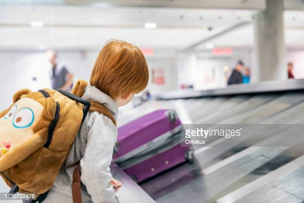 child traveler waiting for suitcase on conveyor belt in airport - luggage rack stock photos and pictures
