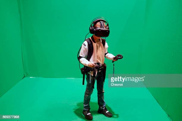 A child tries the virtual reality headset 'HTC Vive' to experience 3D virtual reality as he plays a video game during the 'Paris Games Week' on...