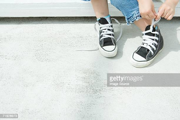 Child tying their shoelaces