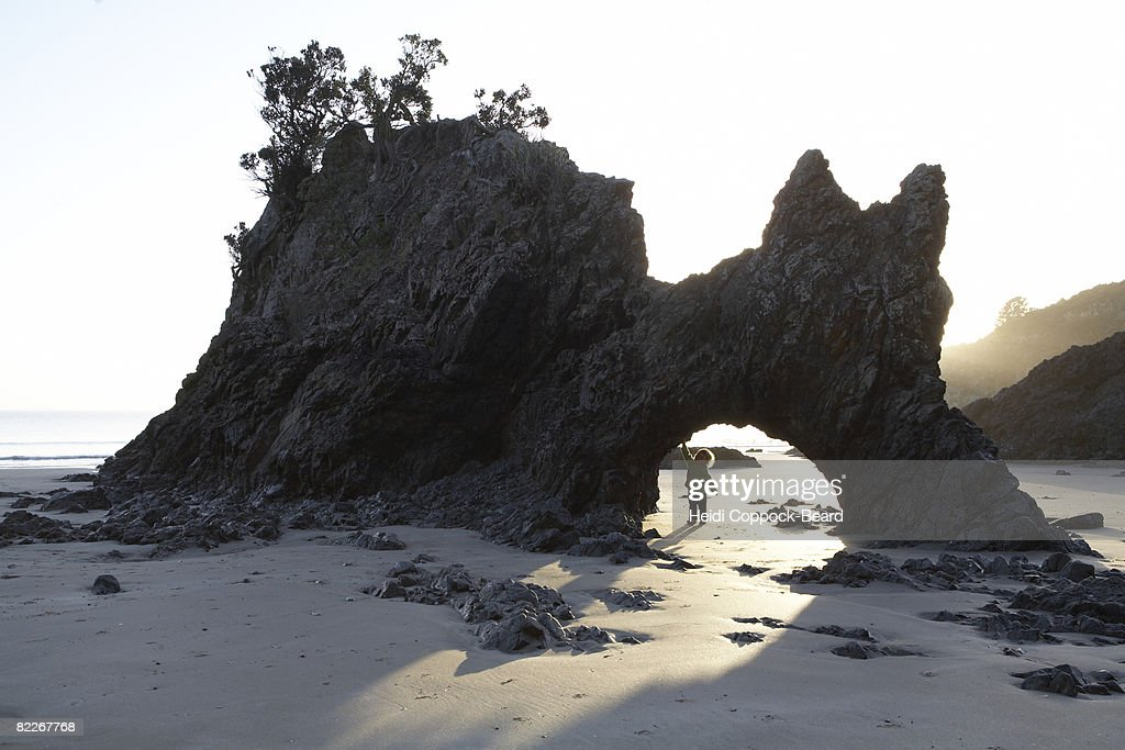 Child under rock formation by the sea : Stock Photo