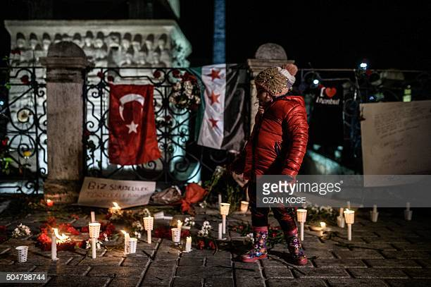 A child understood as Syrian living Istanbul stands in front of a makeshift memorial with flowers candles and a Turkish and a Syrian flag in tribute...