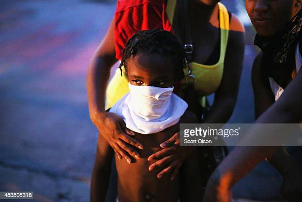 Child uses a rag to shield his face from tear gas being fired by police who used it to force protestors from the business district into nearby...