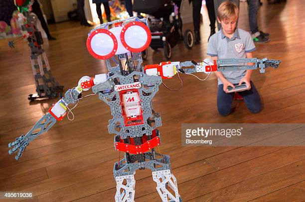 A child uses a tablet device to control the Meccanoid G15 KS robot manufactured by Meccano SA at the Toy Retailers Association DreamToys 2015 event...