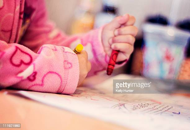 Child uses crayons to color