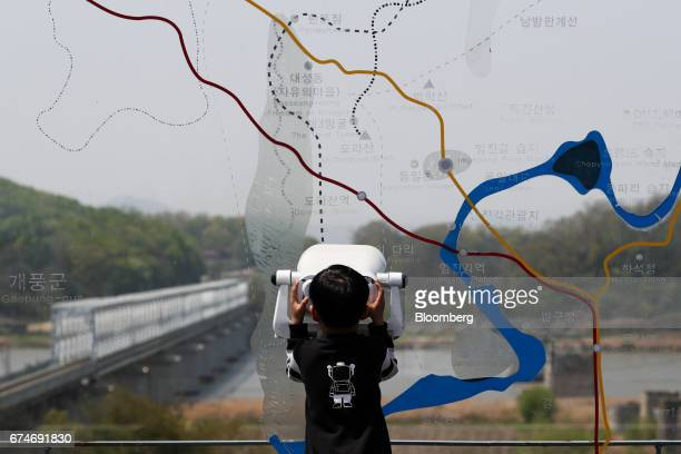 A child using a binocular looks across to the north side of the border at the Imjingak pavilion near the demilitarized zone in Paju South Korea on...