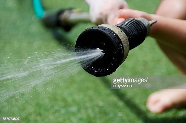 a child using a garden hose pipe - hose stock pictures, royalty-free photos & images
