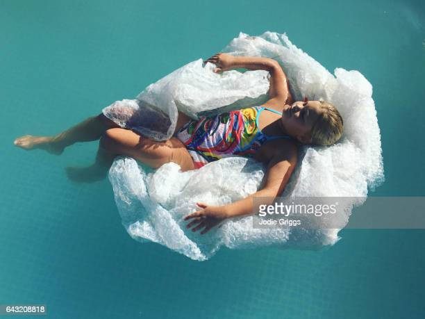 Child using a pile of discarded bubble wrap as an inflatable pool lounge