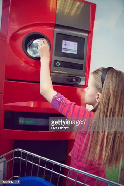 child using a plastic bottle recycling machine - devolver - fotografias e filmes do acervo