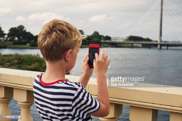 child using a smart phone - southport england stock pictures, royalty-free photos & images