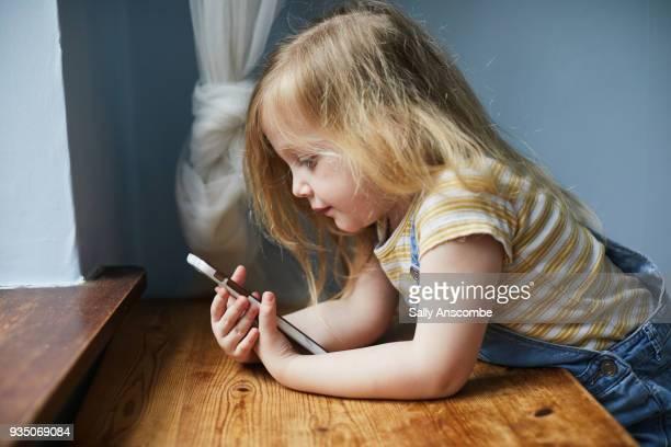 child using a smartphone - ein mädchen allein stock-fotos und bilder