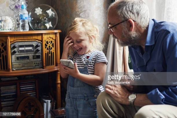 Child using a smartphone with her grandfather