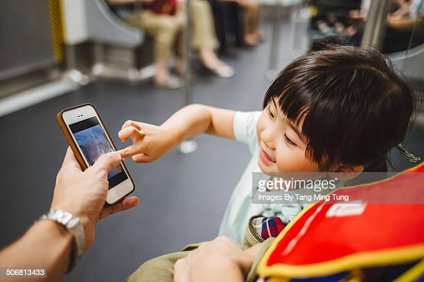 Child using dad's smartphone on train