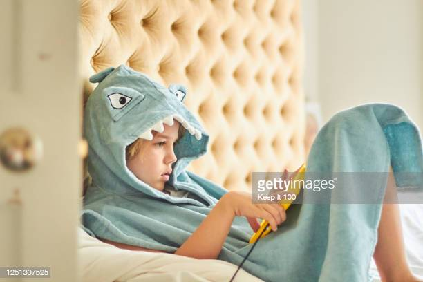 child using digital portable device - bed stock pictures, royalty-free photos & images