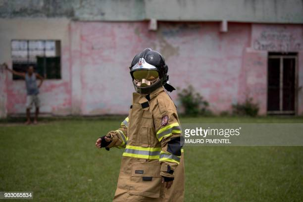 A child using firefighting clothing from Rio's Fire Department plays during a social event organized by the Brazilian Armed Forces at Vila Kennedy...