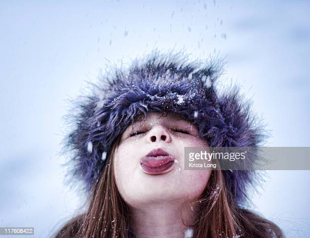 Child using her tongue to catch snowflakes