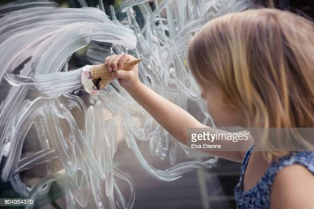 Child using ice cream in a cone, to paint a mess on a window