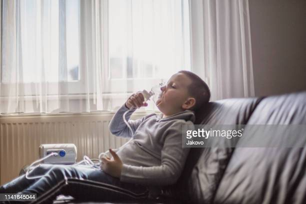 child using inhaler at home - respiratory disease stock pictures, royalty-free photos & images